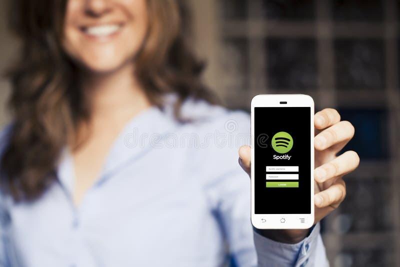 МАЛАГА, ИСПАНИЯ - 26-ОЕ АПРЕЛЯ 2015: Усмехаясь женщина держа мобильный телефон с музыкой App Spotify в экране стоковые фотографии rf