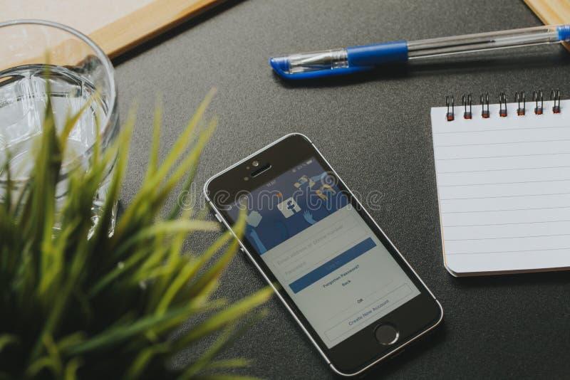 МАЛАГА, ИСПАНИЯ - 6-ОЕ МАРТА 2018: Мобильный телефон с Facebook app в экране, на черном столе близко к веществу офиса стоковые фотографии rf