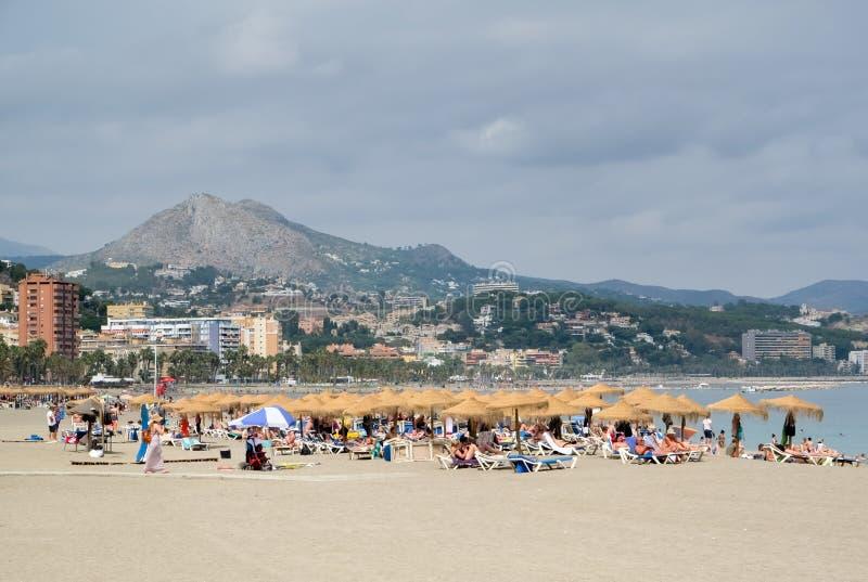 МАЛАГА, ANDALUCIA/SPAIN - 5-ОЕ ИЮЛЯ: Люди ослабляя на пляже стоковые изображения rf