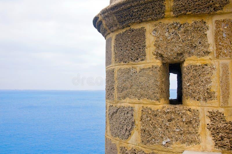 Малая башня кирпича с малыми окнами и видом на море, летом, Испанией стоковое фото