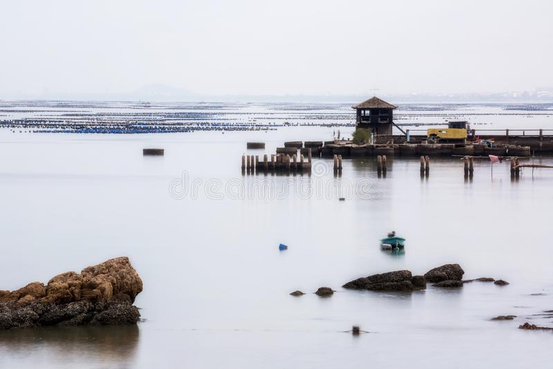 Малая башня на пристани рыбной ловли с ровным голубым морем и отражение неба любят зеркало, съемка долгой выдержки стоковое изображение rf