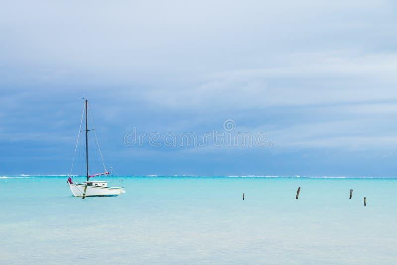 Малая белая шлюпка, причаливающ столбы и море overcast карибское стоковые изображения rf