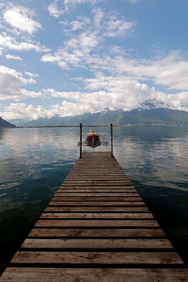 Малая весельная лодка причаленная на женевском озере в Швейцарии стоковые фотографии rf
