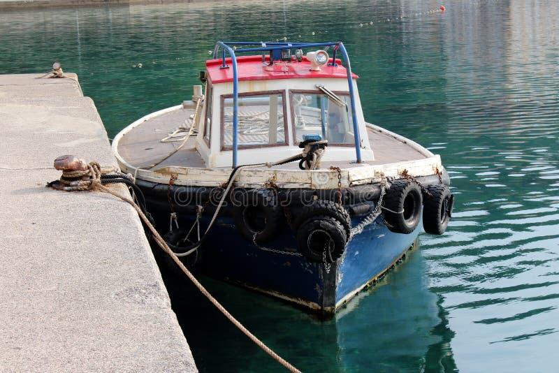 Малая деревенская деревянная рыбацкая лодка связанная на местной пристани стоковая фотография rf