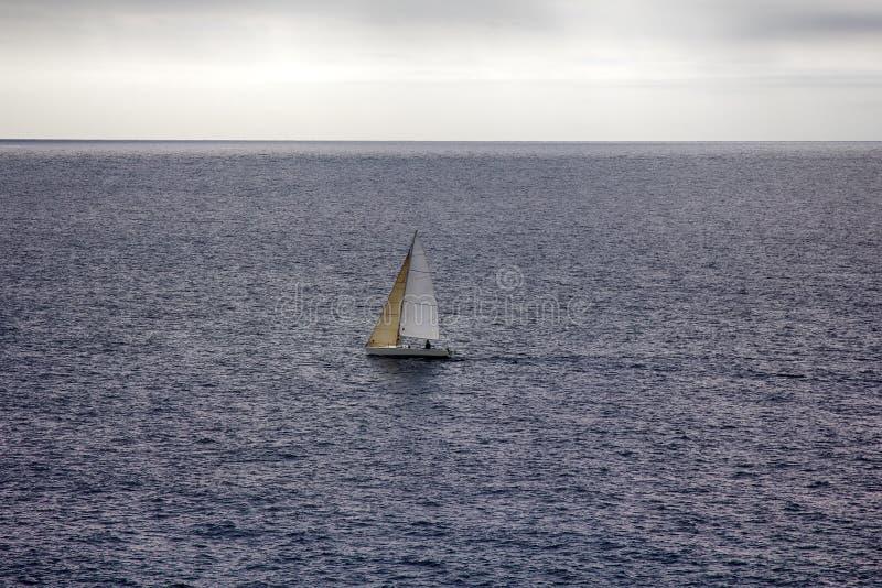 Малая одно-masted яхта плавания на предпосылке слабых волн стоковые изображения rf