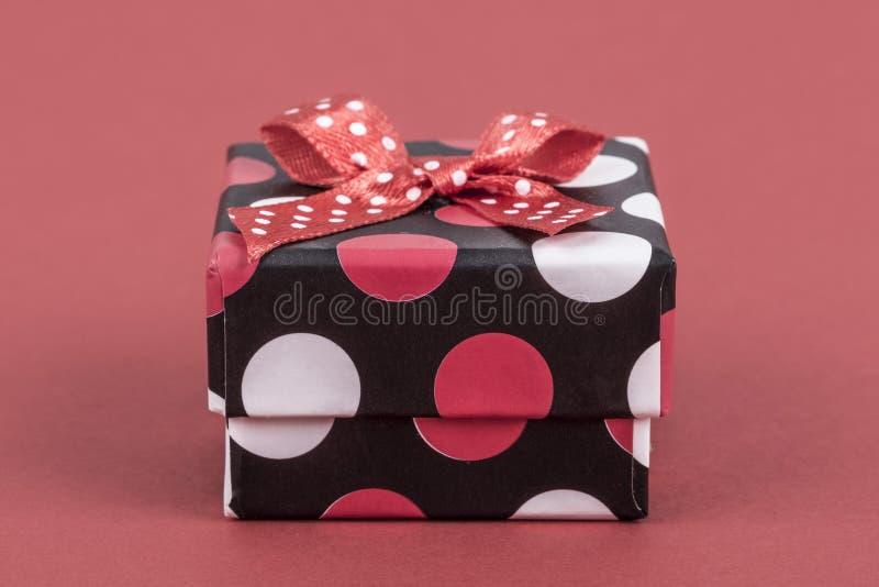 Малая подарочная коробка на красном цвете стоковая фотография