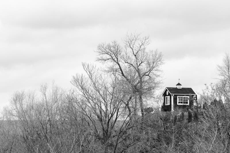 Малая скромная хата na górze высокого холма окруженного к зима чуть-чуть стоковая фотография