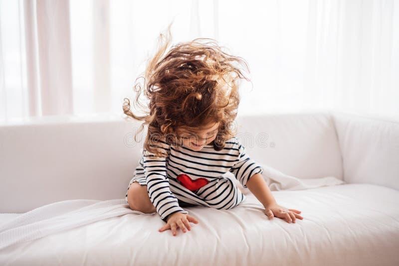 Малая счастливая девушка в striped футболке дома имея потеху стоковое фото rf