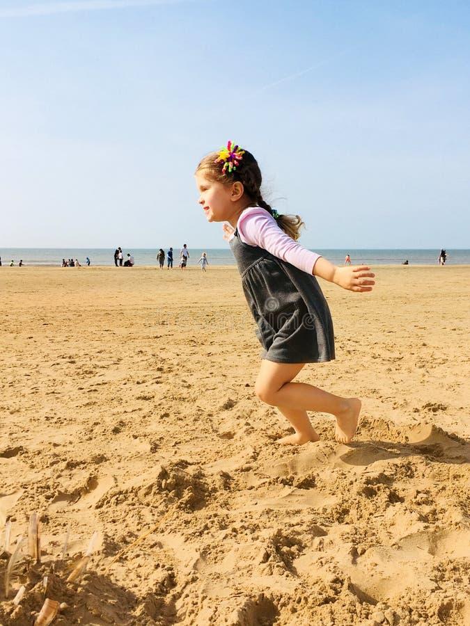 Малая счастливая маленькая девочка бежит barefoot вдоль пляжа стоковая фотография