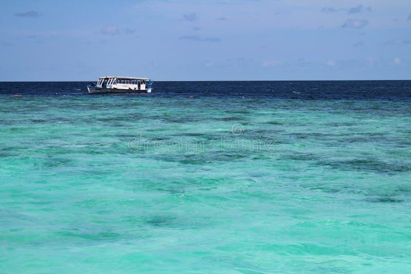 Малая шлюпка Dhoni на голубом океане с ясным небом в Мальдивах стоковые изображения rf
