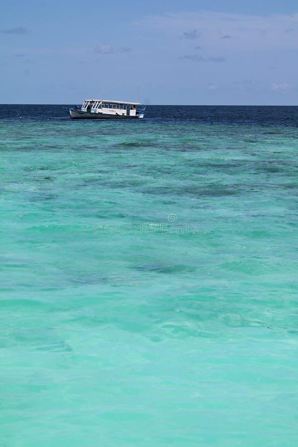 Малая шлюпка Dhoni на голубом океане с ясным небом в Мальдивах стоковое фото rf