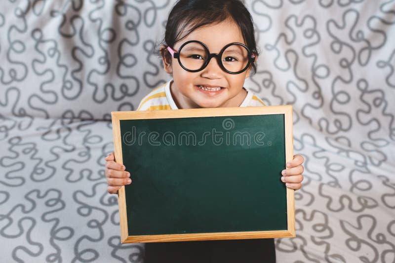 Маленькая азиатка держит чистую доску на диване стоковые фотографии rf