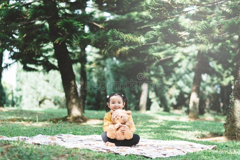 Маленькая азиатка обнимает своего плюшевого медведя в парке стоковое фото