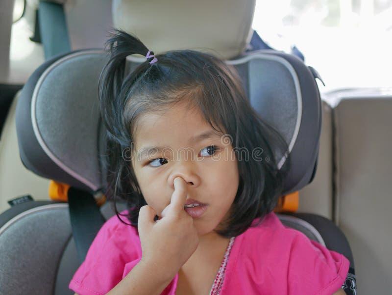 Маленькая азиатская девочка, собирающая свой нос - детская привычка / поведение стоковое изображение