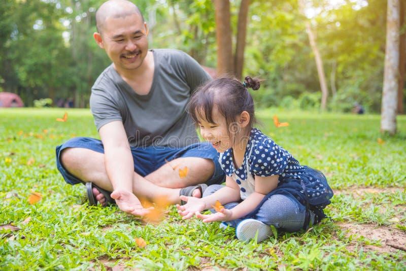 Маленькая азиатская девушка и ее отец смотря бабочек стоковое фото rf