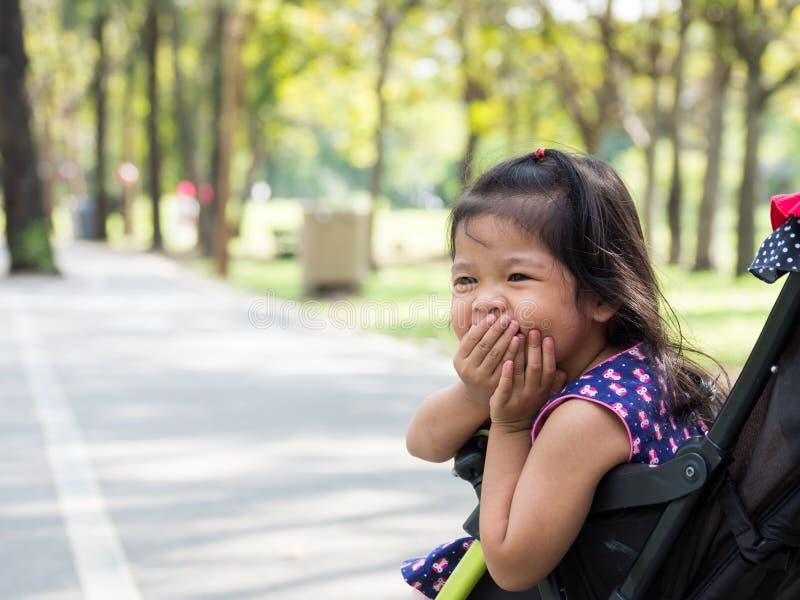 Маленькая азиатская девушка сидя в прогулочной коляске на общественном парке Она смотрит haply и смеяться над и gagging стоковые фото