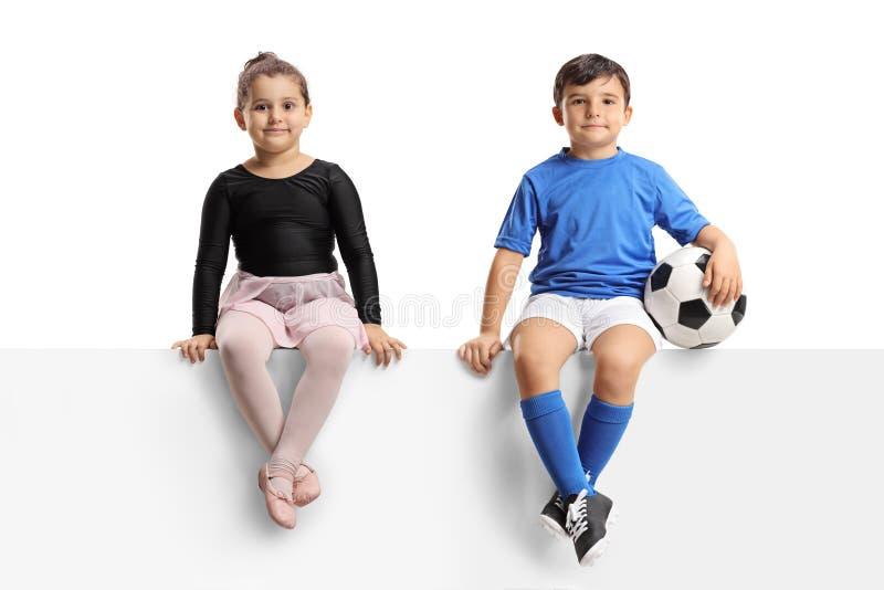 Маленькая балерина и маленький футболист сидя на панели стоковые изображения