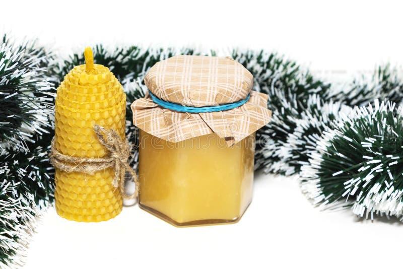 Маленькая банка меда, свеча из натурального воска на белом фоне подарок на новый год стоковое изображение