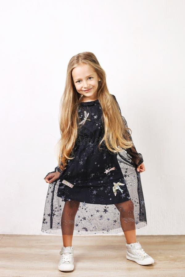 Маленькая белокурая девушка при длинные золотые волосы нося черное платье с звездами & планетами, танцами, smling & имея потеха,  стоковая фотография