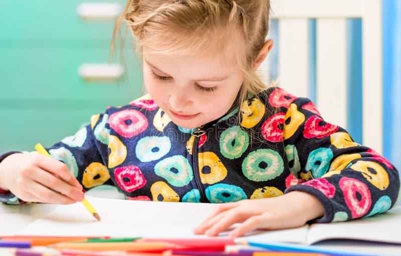 Маленькая белокурая девушка рисует с карандашами стоковые фото