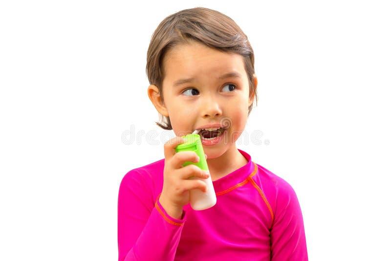 Маленькая больная девушка использовала медицинский брызг для дыхания стоковое фото rf
