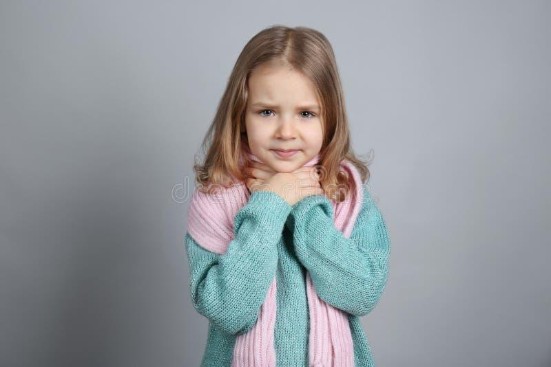 Маленькая больная девушка с болью в горле на предпосылке цвета стоковая фотография
