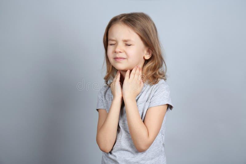 Маленькая больная девушка с болью в горле на предпосылке цвета стоковое фото