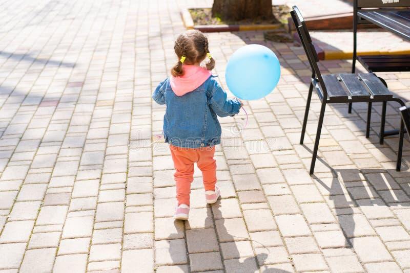 Маленькая девочка бежит далеко от ее родителей с раздувным шариком в их руках стоковое изображение rf