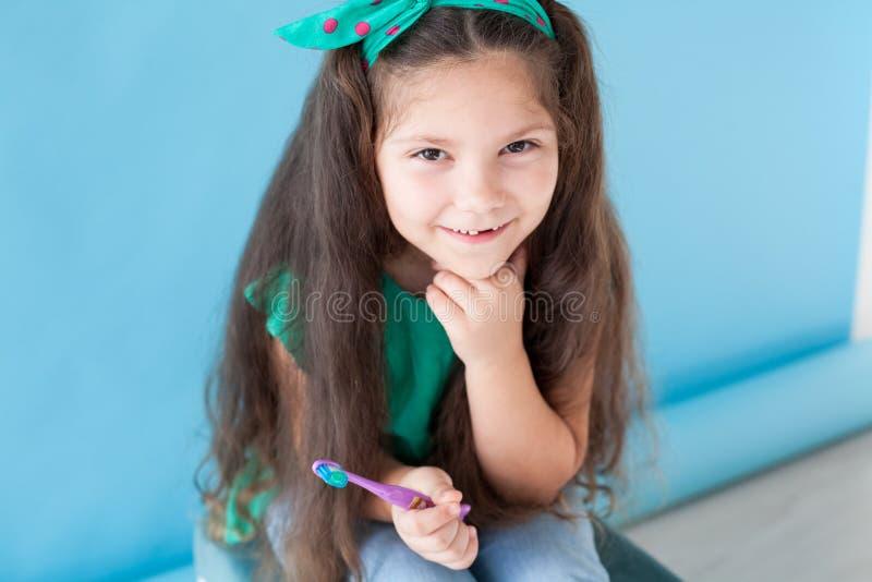 Маленькая девочка без зубов с зубной щеткой в зубоврачевании стоковые фотографии rf