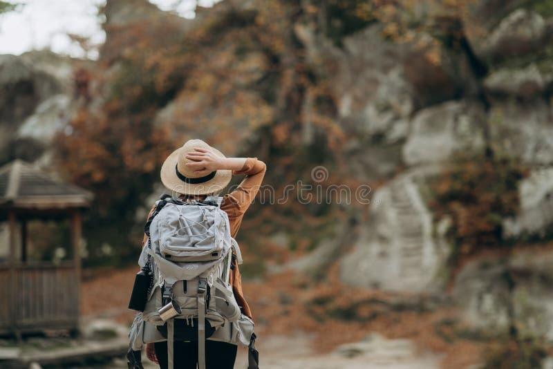 Маленькая девочка битника с рюкзаком наслаждаясь заходом солнца на пиковой горе стоковые фотографии rf