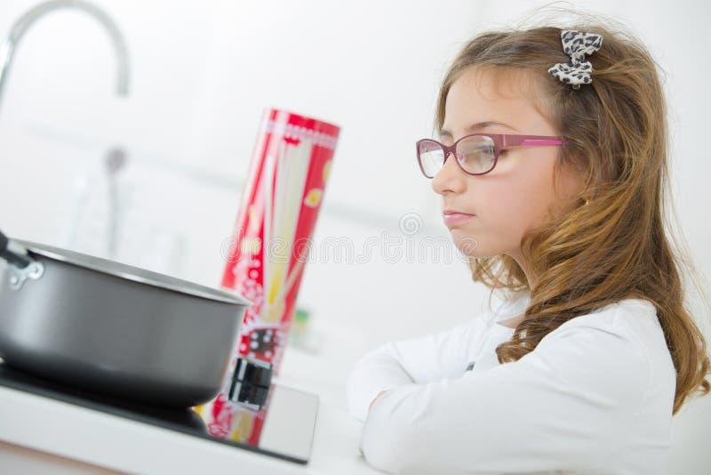 Маленькая девочка варя макаронные изделия стоковое фото