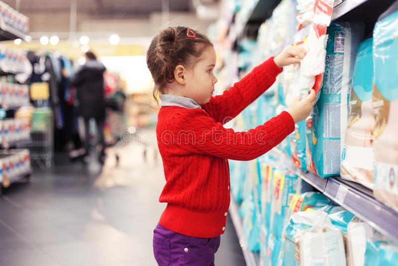 Маленькая девочка выбирает пеленки в супермаркете стоковая фотография