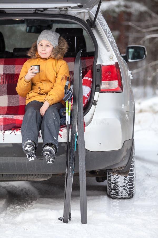 Маленькая девочка выпивает горячий чай после кататься на лыжах пока сидящ в хоботе автомобиля suv Деятельность при зимы стоковое изображение rf