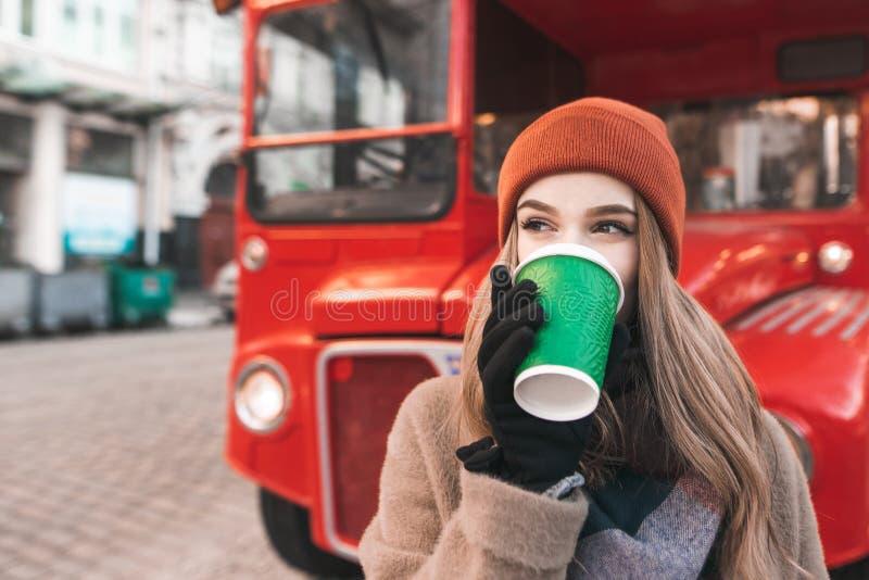 Маленькая девочка выпивает кофе от чашки зеленой книги против красной предпосылки и взглядов автобуса к стороне Привлекательная д стоковые фотографии rf