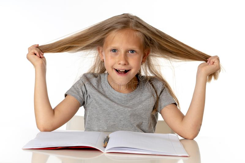 Маленькая девочка вытягивая ее волосы в стрессе и над работаемой концепцией образования стоковое изображение