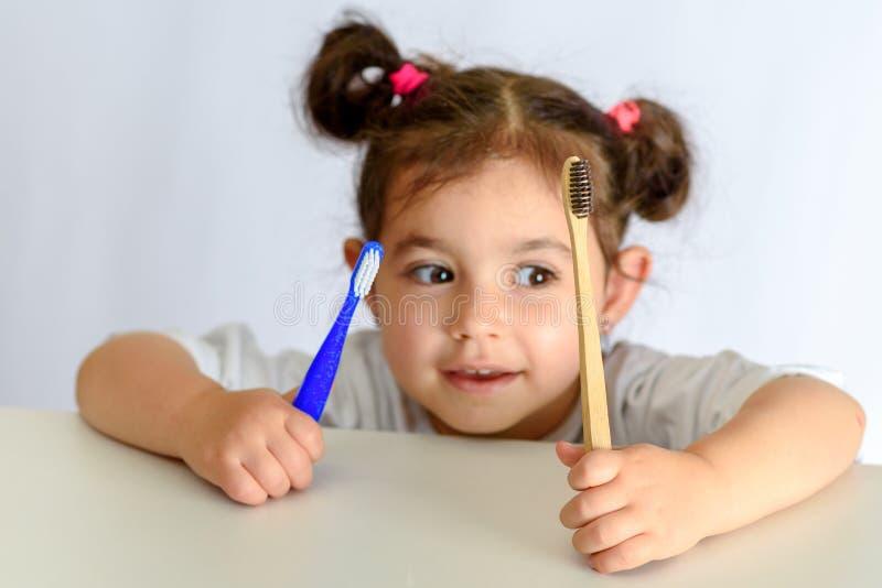 Маленькая девочка в белой рубашке держа бамбуковую зубную щетку и пла стоковая фотография