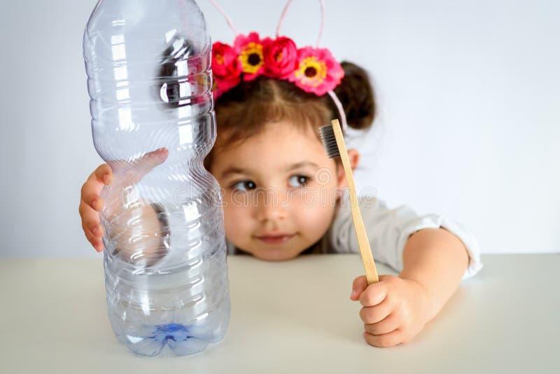 Маленькая девочка в белой рубашке держа бамбуковую зубную щетку и пла стоковые изображения