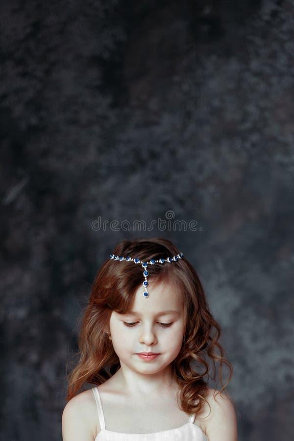 Маленькая девочка в белом платье в комнате молит стоковая фотография rf