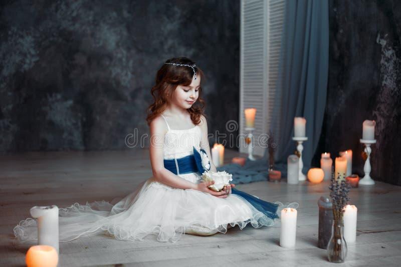 Маленькая девочка в белом платье в комнате с детьми свечей молит стоковое фото rf