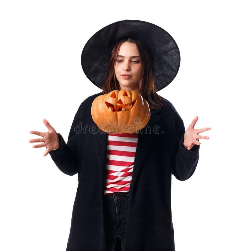 Маленькая девочка в взметнутой черной шляпе, заполненной тыкве, изолированной на белой предпосылке стоковые изображения