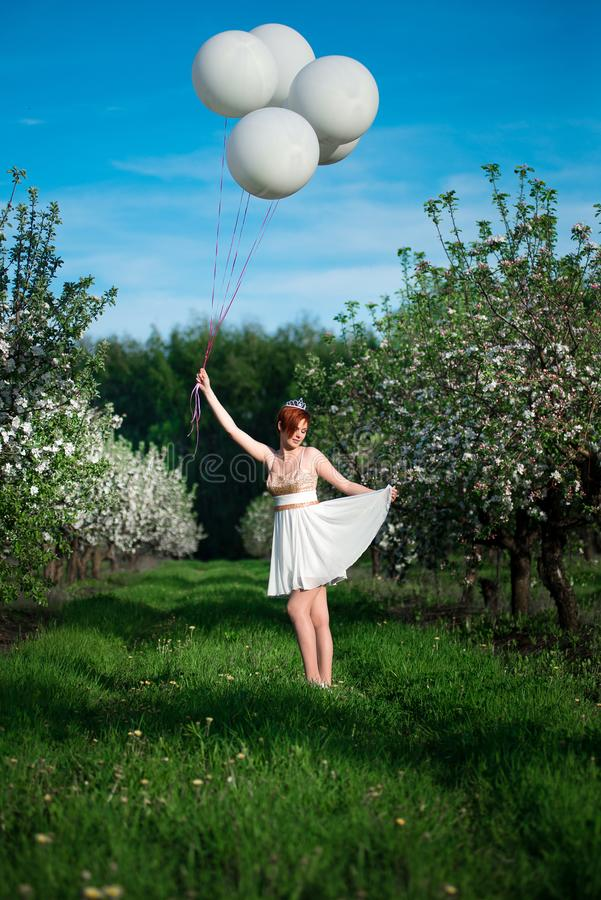 Маленькая девочка в зеленом саде держа огромные воздушные шары стоковые изображения