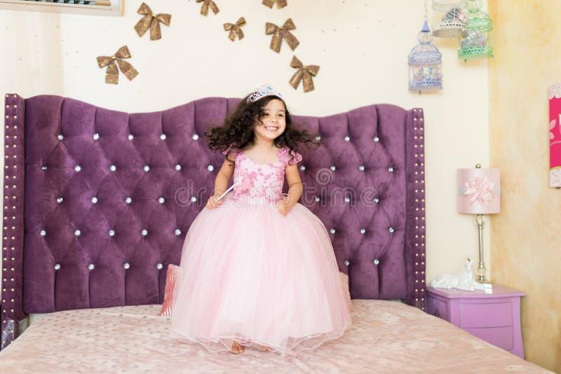 Маленькая девочка в королевском костюме на кровати стоковые изображения rf