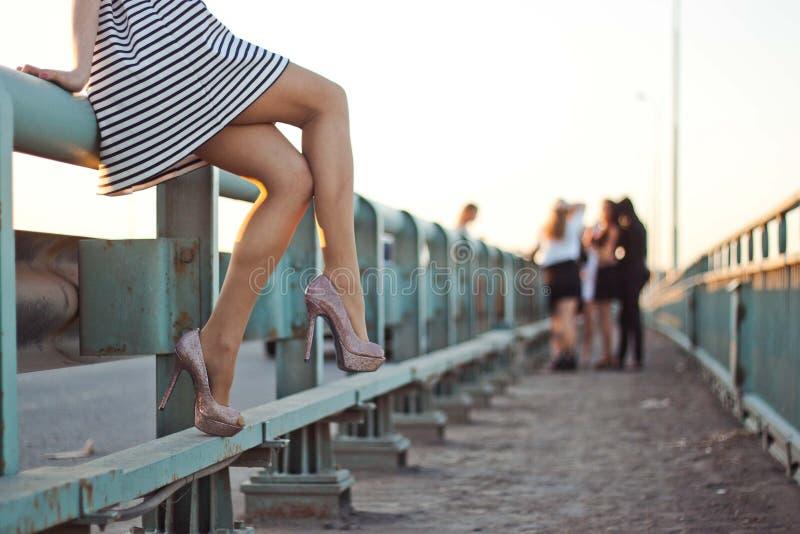 Маленькая девочка в коротком платье и ботинках сидит на мосте Концепция завистливости, сплетни, проблем ` s женщин или праздника стоковая фотография