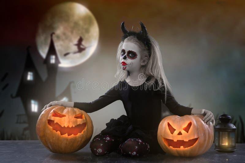 Маленькая девочка в костюме ведьмы представляя с тыквами над fairy предпосылкой halloween стоковые фотографии rf