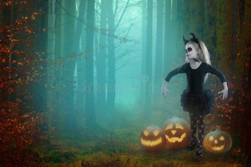 Маленькая девочка в костюме ведьмы представляя с тыквами над fairy предпосылкой halloween стоковая фотография