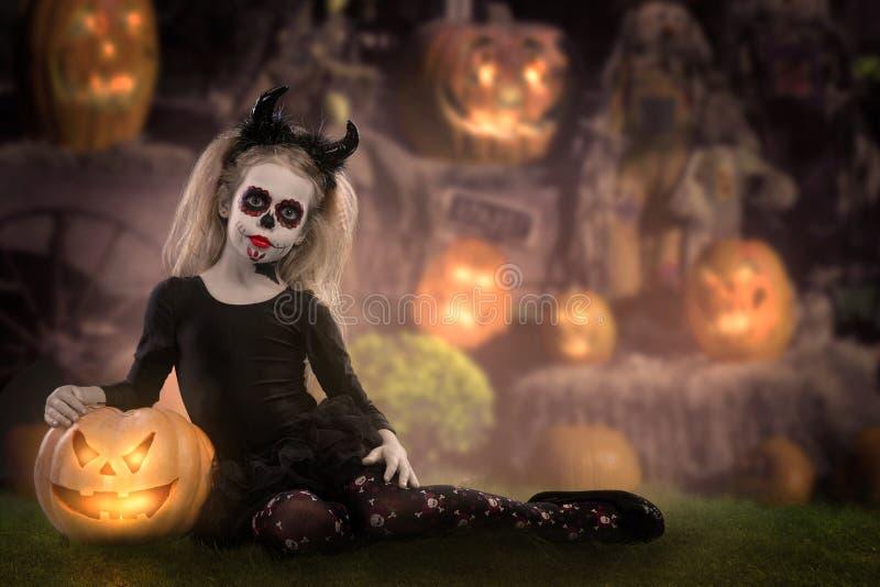 Маленькая девочка в костюме ведьмы представляя с тыквами над fairy предпосылкой halloween стоковое фото rf