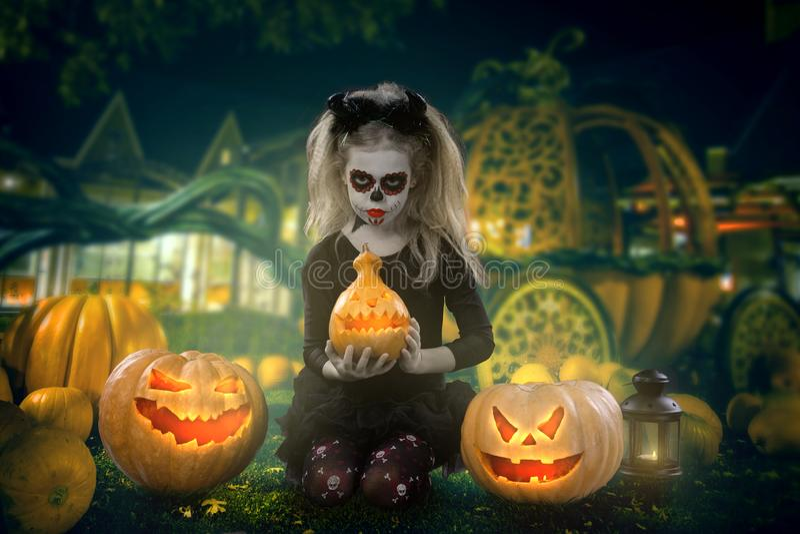Маленькая девочка в костюме ведьмы представляя с тыквами над fairy предпосылкой halloween стоковая фотография rf