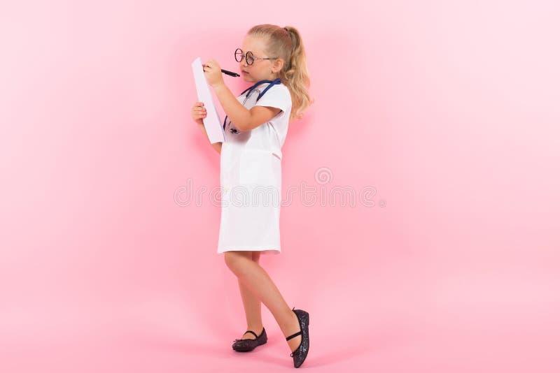 Маленькая девочка в костюме доктора с бумагой стоковая фотография