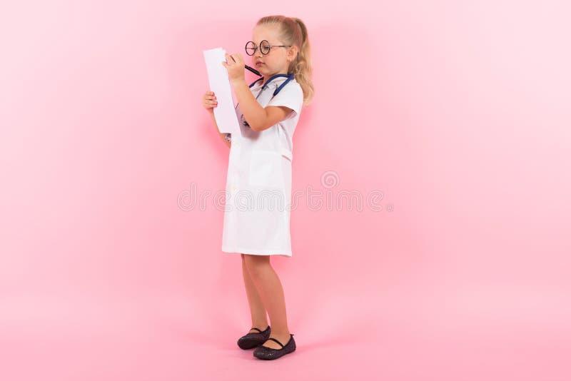 Маленькая девочка в костюме доктора с бумагой стоковая фотография rf