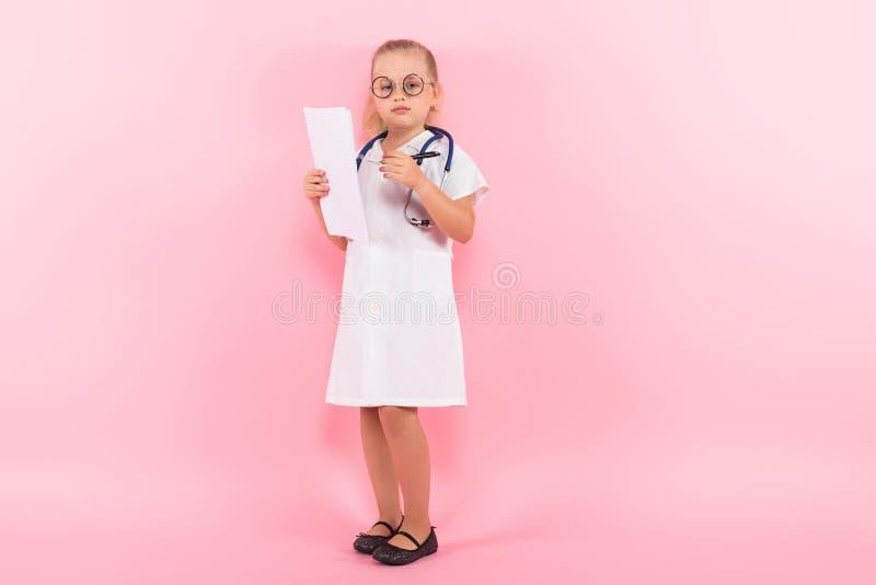 Маленькая девочка в костюме доктора с бумагой стоковые изображения